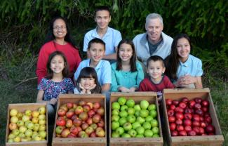A picture of the Polly family with boxes of various apples.